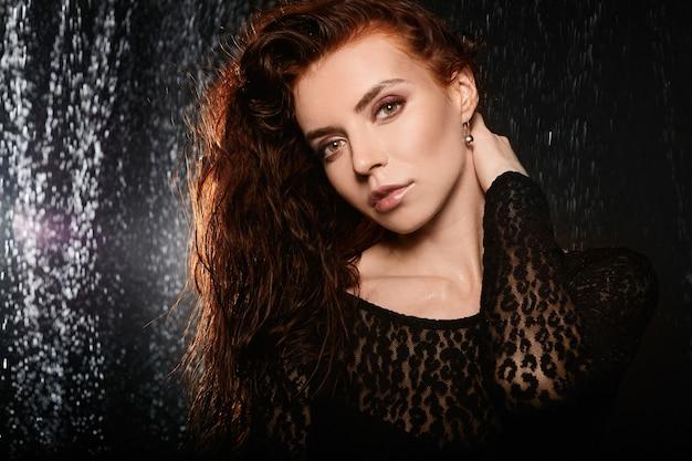Młoda kobieta z rude włosy i idealny modny makijaż pozowanie na ciemnym tle. piękna modelka z modnym nagim makijażem. pojęcie piękna i gładkiej skóry