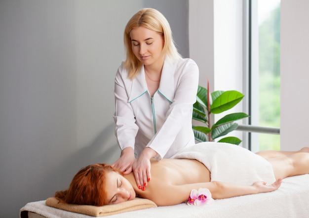 Młoda kobieta z rudymi włosami otrzymuje terapeutyczny masaż pleców