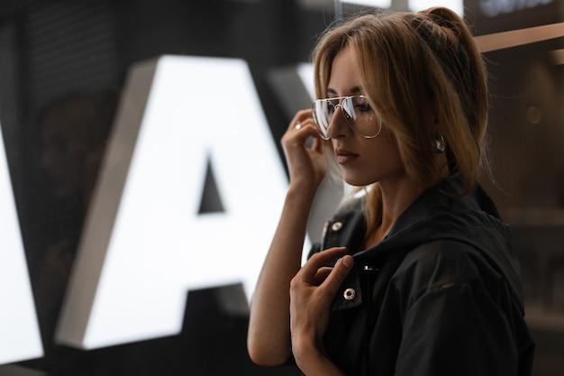 Młoda kobieta z rudymi włosami w modnej kurtce w modnych okularach pozuje przy szklanej ścianie w sklepie. nowoczesna amerykańska modelka w pomieszczeniu. styl uliczny.