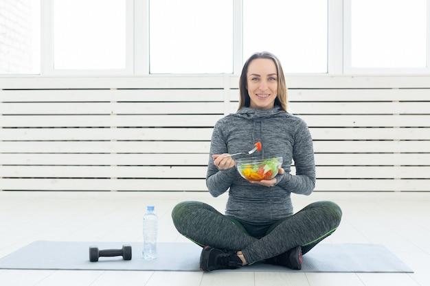 Młoda kobieta z sałatką i hantle, siedząc na podłodze