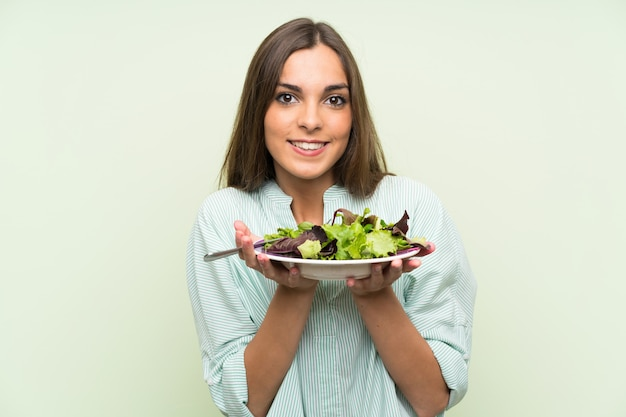 Młoda kobieta z sałatką nad odosobnioną zieleni ścianą