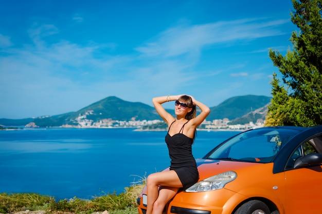 Młoda kobieta z samochodem po stronie morza