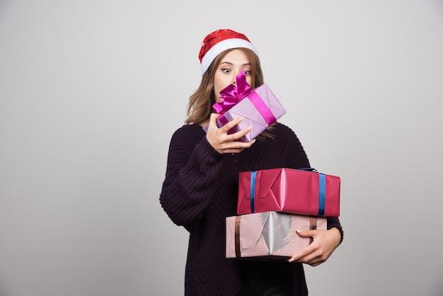 Młoda kobieta z santa kapeluszem przewożącym pudełka prezenty.