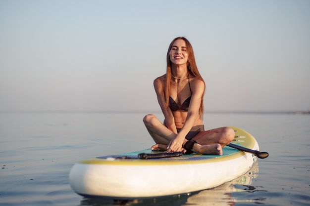 Młoda kobieta z seksownym dopasowanym ciałem pozowanie na desce wiosła w morzu
