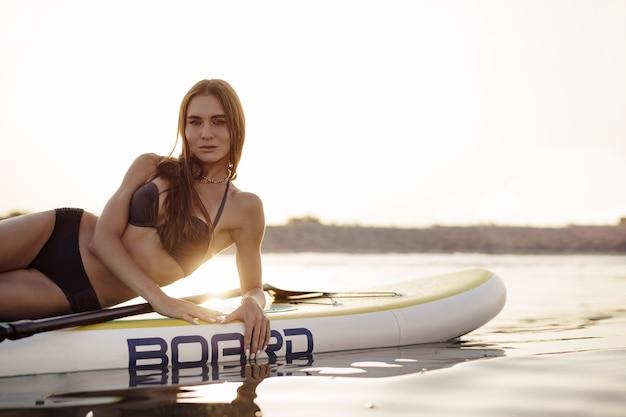 Młoda kobieta z seksownym dopasowanym ciałem pozowanie na desce wiosłowej na morzu, zbliżenie