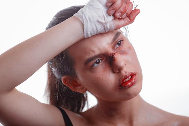 Młoda kobieta z siniakami na twarzy ofiarą przemocy domowej na białym tle