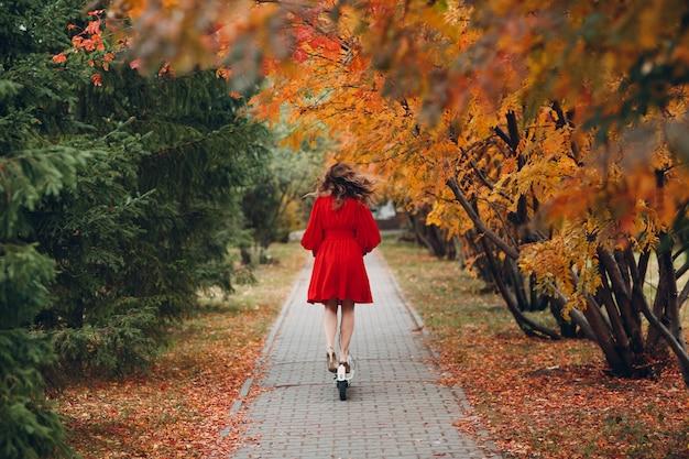 Młoda kobieta z skuterem elektrycznym w czerwonej sukience w jesiennym parku miejskim.