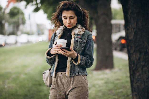 Młoda kobieta z słuchanie muzyki i picia kawy
