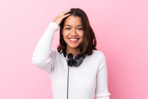 Młoda kobieta z słuchawkami nad odosobnioną menchii ścianą z niespodzianką i zszokowanym wyrazem twarzy