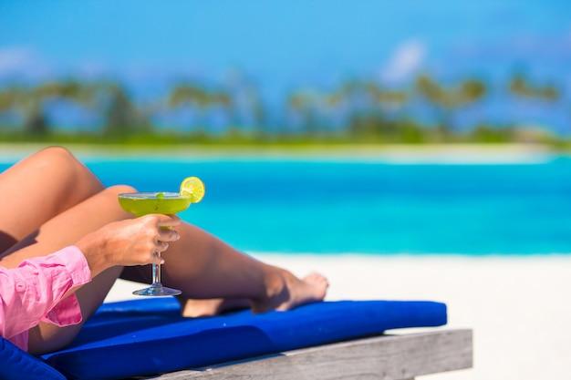 Młoda kobieta z smakowitym koktajlem na białej tropikalnej plaży