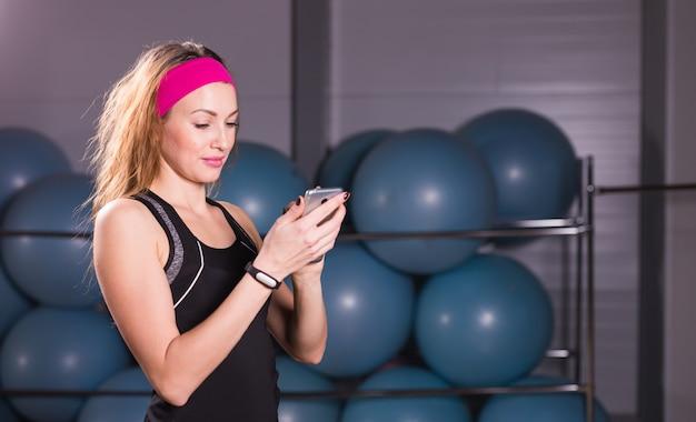 Młoda kobieta z smartphone i tracker fitness na siłowni, przerwa na trening