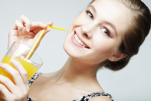 Młoda kobieta z sokiem pomarańczowym