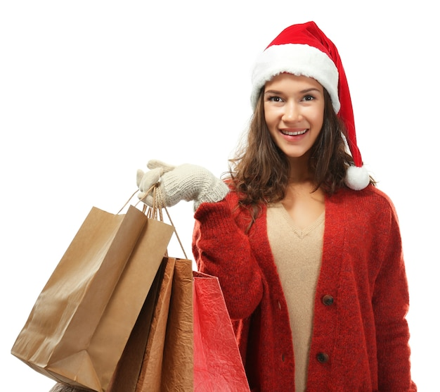 Młoda kobieta z świątecznymi zakupami na białym tle