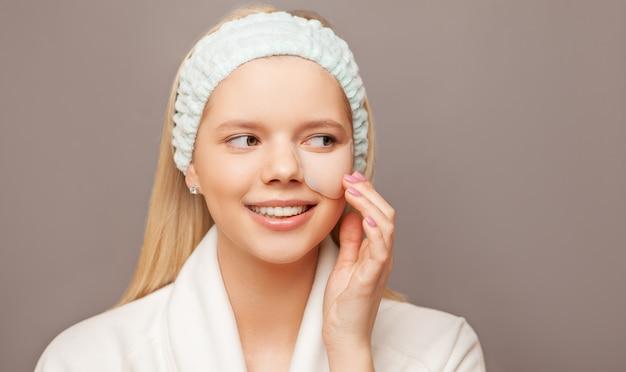 Młoda kobieta z świeżą zdrową skórą i włosami używać łaty i ono uśmiecha się.