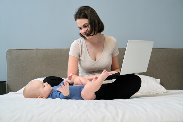 Młoda kobieta z synem malucha siedzi w łóżku z laptopem, matka freelancerka, trener, blogerka pracująca w domu