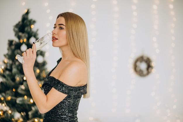 Młoda kobieta z szampanem przy choince