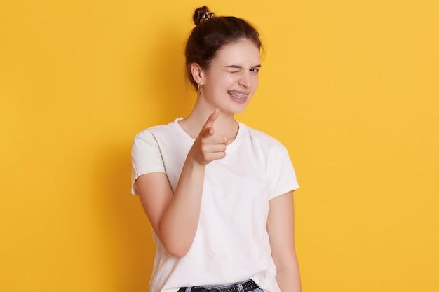 Młoda kobieta z szczęśliwy wyraz twarzy pozowanie na białym tle nad żółtą ścianą