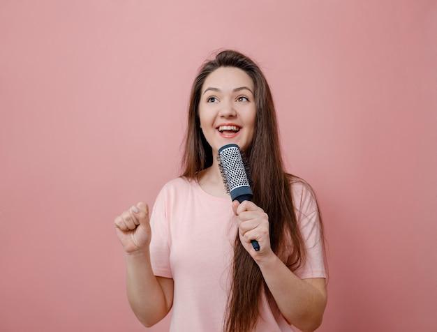 Młoda kobieta z szczotką do włosów jak z mikrofonem w ręku na różowym tle