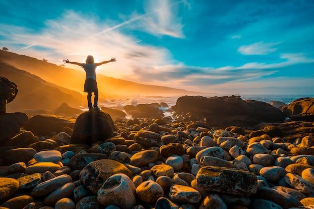 Młoda kobieta z szeroko otwartymi ramionami o zachodzie słońca na wybrzeżu jaizkibel niedaleko san sebastian. kraj basków