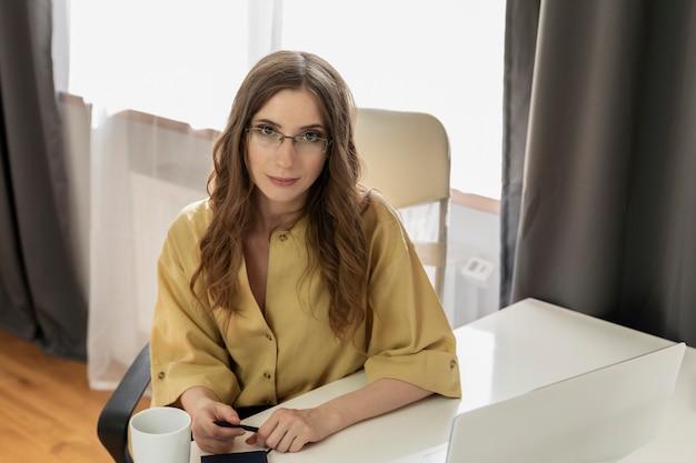 Młoda kobieta z szkłami pracuje w biurze
