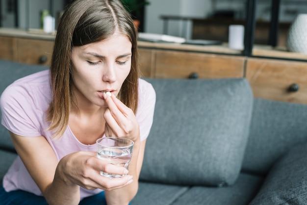 Młoda kobieta z szklanką wody biorąc lek