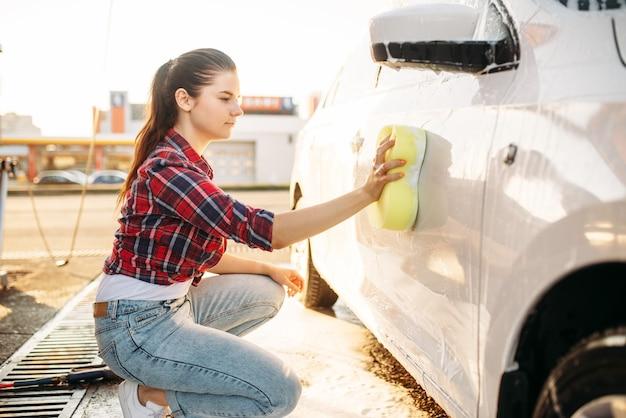 Młoda kobieta z szorowaniem pojazdu gąbką z pianką, myjnia samochodowa. pani na samoobsługowym myciu samochodów. myjnia zewnętrzna w letni dzień