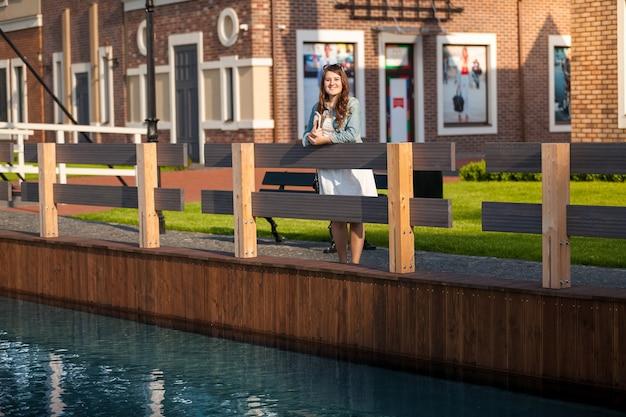 Młoda kobieta z tabletem na moście w amsterdamie