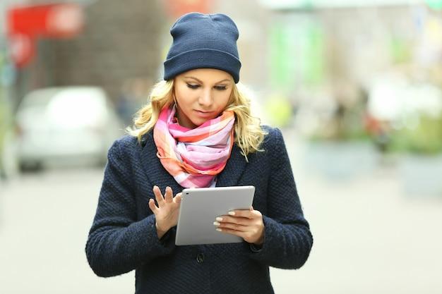Młoda kobieta z tabletem na ulicy miasta