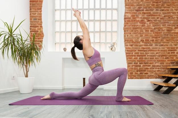 Młoda kobieta z tatuażami robi ćwiczenia jogi w domu. pojęcie sportu i zdrowego stylu życia.