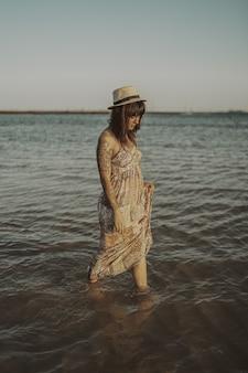 Młoda kobieta z tatuażami ubrana w sukienkę i słomkowy kapelusz na zamazanym oceanie