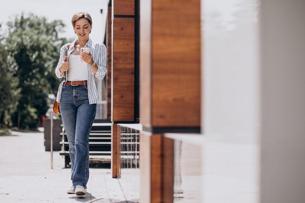 Młoda kobieta z telefonem i komputerem spacerująca poza ulicą