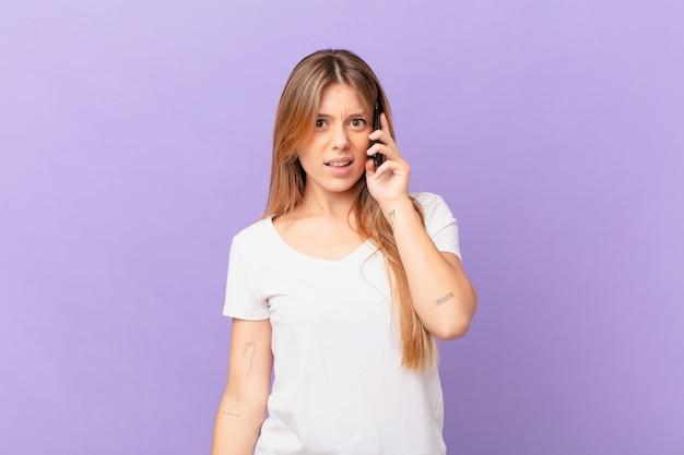 Młoda kobieta z telefonem komórkowym czuje się zakłopotana i zdezorientowana