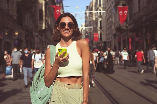 Młoda kobieta z telefonem komórkowym przemierza zatłoczone ulice stambułu, ciesząc się pięknem miasta
