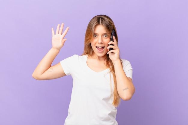 Młoda kobieta z telefonem komórkowym uśmiechnięta radośnie, machająca ręką, witająca i witająca cię