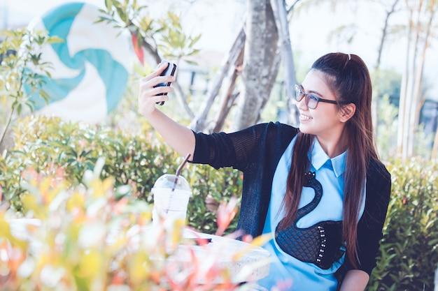 Młoda kobieta z telefonem komórkowym w podwórku