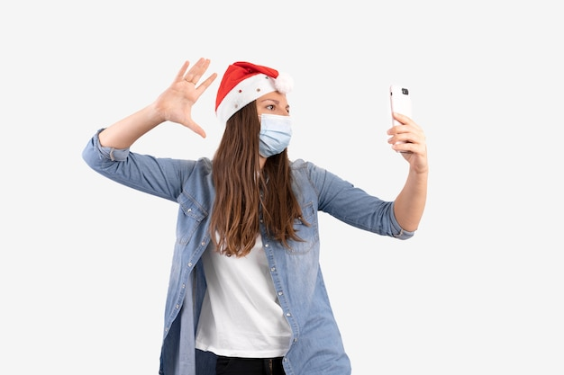 Młoda kobieta z telefonem, maską medyczną i czapką mikołaja. świąteczne zakupy online na kwarantannie.
