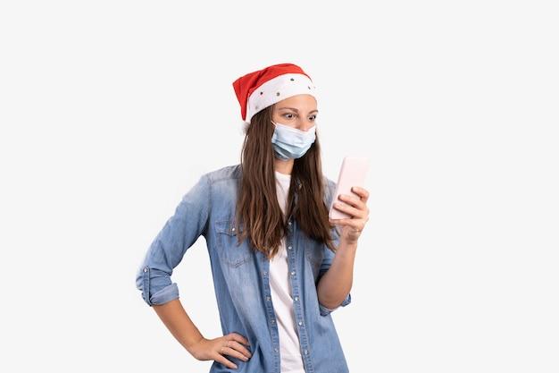 Młoda kobieta z telefonem, maską medyczną i czapką mikołaja