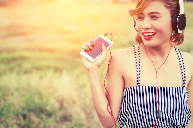 Młoda kobieta z telefonu i słuchawek