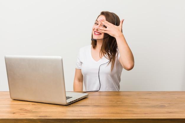 Młoda kobieta z telemarketeru mruga przez palce, zakłopotana zakrywająca twarz.