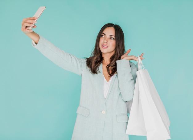 Młoda kobieta z torba na zakupy bierze selfie