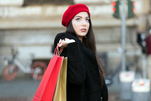 Młoda kobieta z torba na zakupy i bożenarodzeniowym prezentem w mediolan, włochy