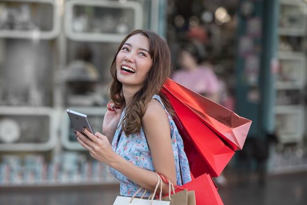 Młoda kobieta z torba na zakupy i smartphone w jej ręce przy centrum handlowym.