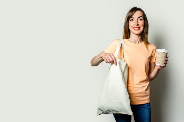 Młoda kobieta z torba na zakupy i trzyma papierową filiżankę z kawą na lekkim tle