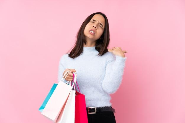 Młoda kobieta z torbą na zakupy na białym tle różowy z wypowiedzi zmęczony i chory