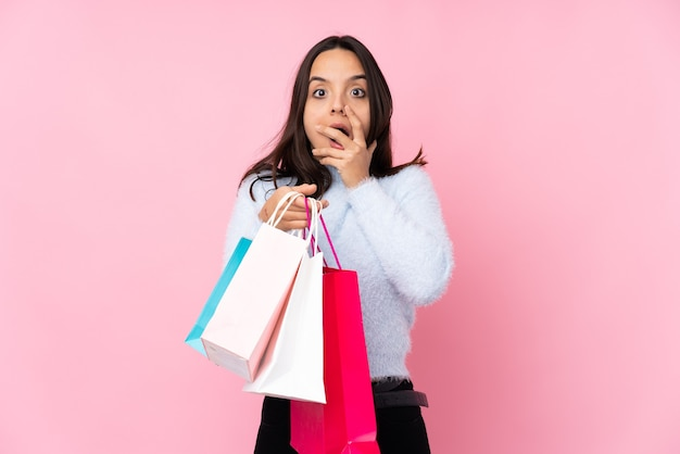 Młoda kobieta z torbą na zakupy na białym tle różowy zaskoczony i zszokowany, patrząc w prawo