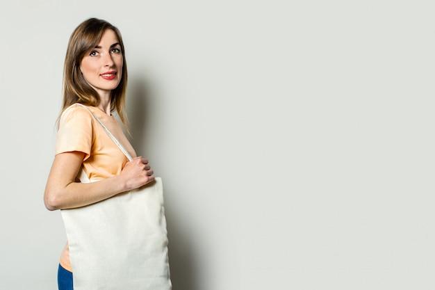 Młoda kobieta z torba na zakupy na jego ramieniu na lekkim tle