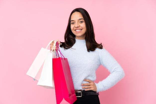 Młoda kobieta z torbą na zakupy na pojedyncze różowe ściany pozowanie z rękami na biodrze i uśmiechnięty