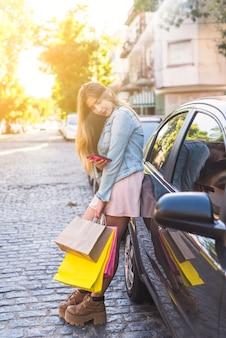 Młoda kobieta z torba na zakupy używać smartphone przy samochodem