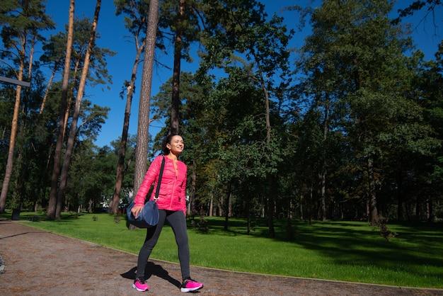 Młoda kobieta z torbą sportową na ramieniu przechodzi obok nas w parku.