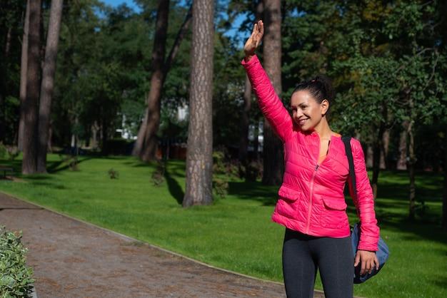 Młoda kobieta z torbą sportową na ramieniu stoi w parku, macha i uśmiecha się.